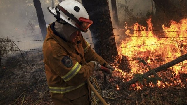 A Rural Fire Service fire-fighter sprays water onto a small fire burning near a home in the Blue Mountains suburb of Faulconbridge