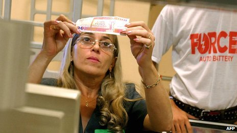 Cuban cashier inspects a Cuban convertible peso note at a supermarket in Havana on 10 November 2004