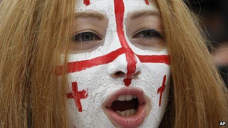 A Georgian woman with face painted in colours of the Georgian flag, attends a rally
