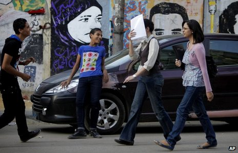 A woman covers her face as she walks past two youths near Tahrir Square in Cairo (9 May 2013)