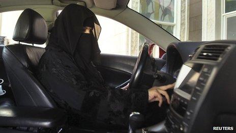 A Saudi woman wearing a burka drives a car