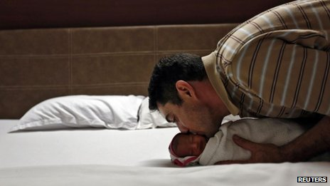 British father kisses his new baby, carried by a surrogate mother in India