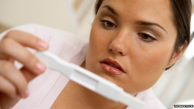 Posed photo of woman looking at pregnancy test