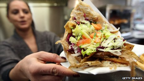 An employee of a doner kebab stand serves a doner sandwich in Berlin, Germany (23 February 2013)