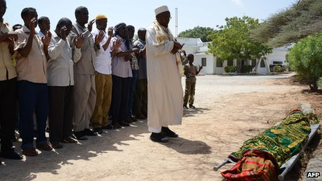 People pray over the body of slain Somali journalist, Abdihared Osman Adan, who was working with Radio Shabelle, before he is laid to rest in the Somali capital, Mogadishu (18 January 2013)