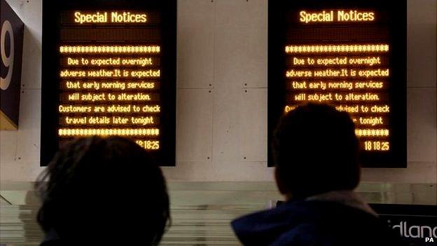 Rail passengers at Euston station looking at signs