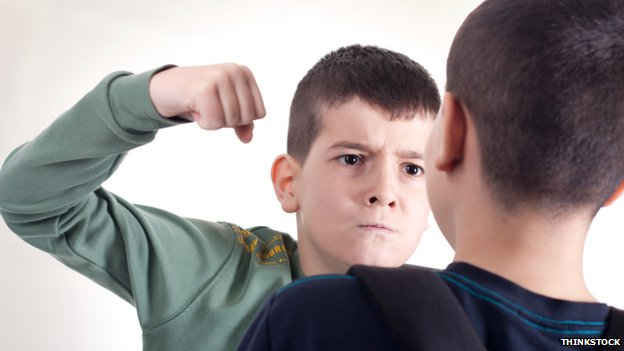 A boy threatening another boy