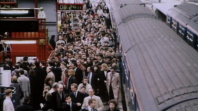 Passengers get off a train onto a crowded platform