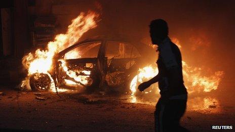 A man looks at a car on fire at the site of a bomb attack in Baghdad on 7 October 2013