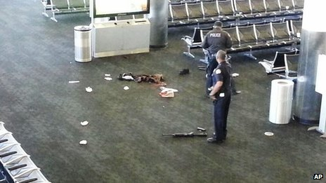 In this photo provided to AP, which has been authenticated based on its contents and other AP reporting, police officers stand near an unidentified weapon in Terminal 3 of the Los Angeles International Airport on 1 November 2013