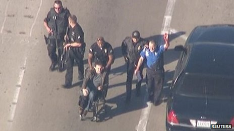 Police escort a man in a wheelchair toward medical help during an incident in which shots were fired at Los Angeles International Airport in Los Angeles in this still image taken from video provided by KNBC November 1, 2013.