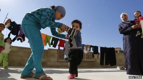 A Syrian refugee girl helps her brother, who the family suspects has polio, to walk