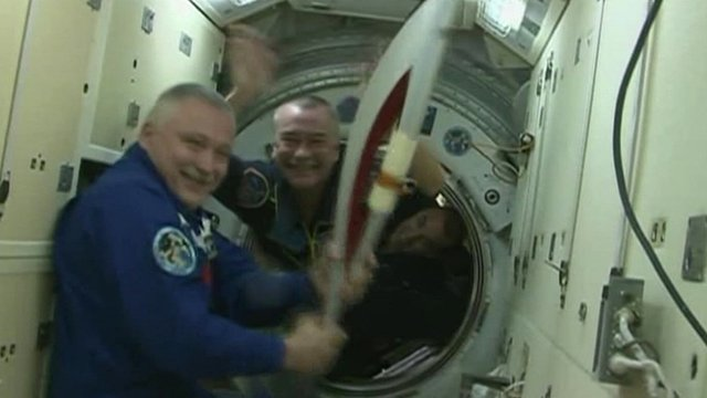 Cosmonauts and astronaut with Sochi torch on board the ISS
