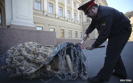 Artist Pyotr Pavlensky lies on the ground, wrapped in barbed wire roll, during a protest action in St Petersburg on 3 May 2013