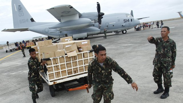 Military personnel deliver aid supplies which arrived in Tacloban