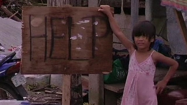 """A young girl stands beside a sign reading """"Help"""""""