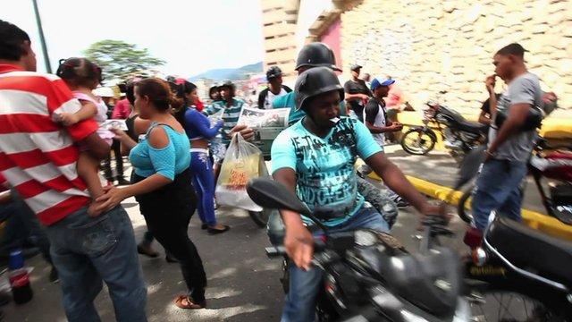 Motorbike weaving through a crowd