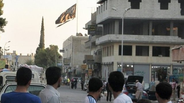 Men look at a large black flag of al-Qaeda flying in Raqqa (30 September 2013)