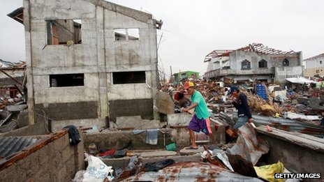 Survivors walk through typhoon hit village on in Tanauan, Leyte, 16 November