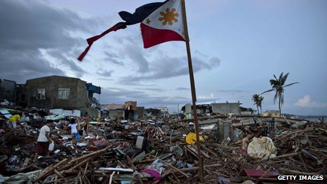 A torn Philippines flag stands in the rubble in the aftermath of Typhoon Haiyan in Tacloban, 16 November