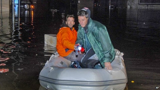 Two men use an inflatable dingy to get around in a flooded street in Olbia