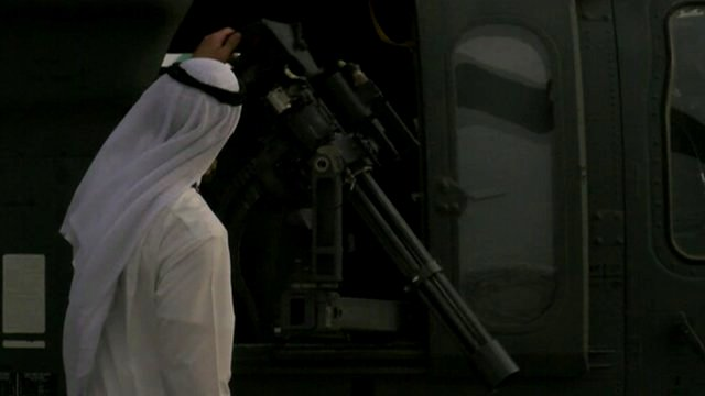 Middle eastern man inspecting a machine gun