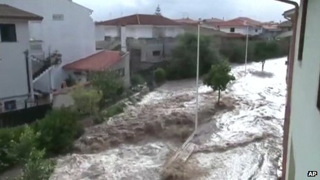 Flood water gushes down a street in Sardinia following a huge rainstorm