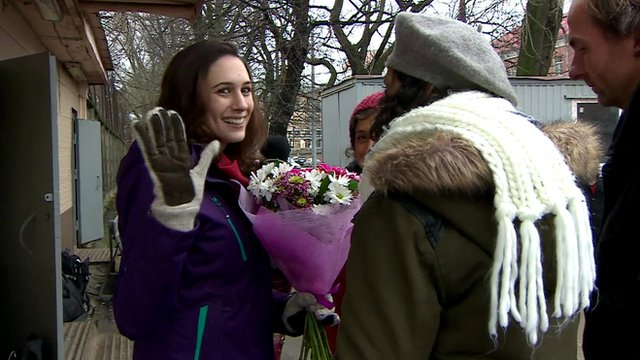 Alex Harris of Greenpeace waves as she leaves prison