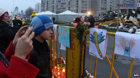 People gather at scene of supermarket collapse in Riga on 23 November 2013