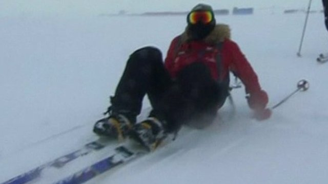 Prince Harry sits on snow in skis after falling over