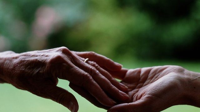 Hand of an elderly woman touching the hand of a younger person