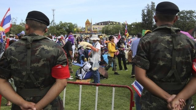 Thai soldiers, foreground, watch anti-government protesters gathering at the Royal Thai Army compound in Bangkok