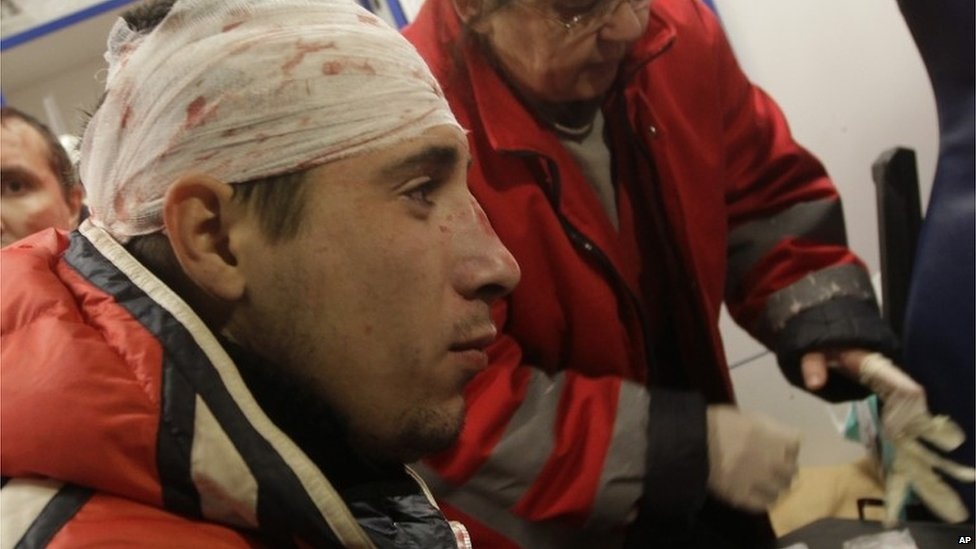 A protester receives medical help in ambulance after Ukrainian riot police broke up a rally