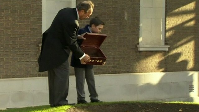 Boy pouring chest of soil into hole at site of memorial garden