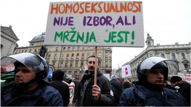"""Protester holds sign reading """"Homosexuality is not a choice, hate is a choice"""" in Zagreb"""