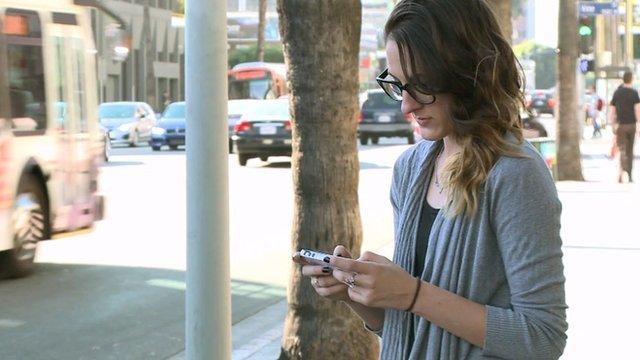 Woman uses phone in street