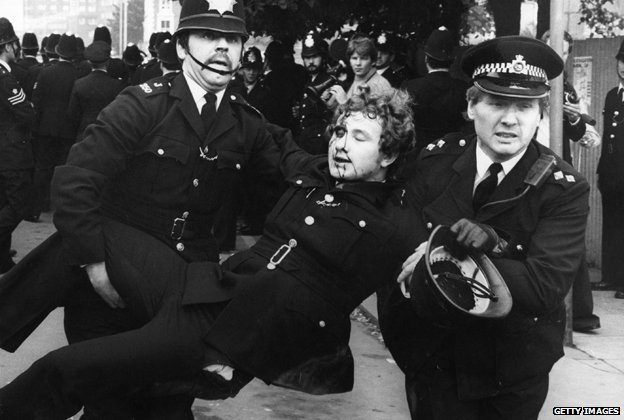 Police officers carry an injured colleague away from the Lewisham riots in 1977