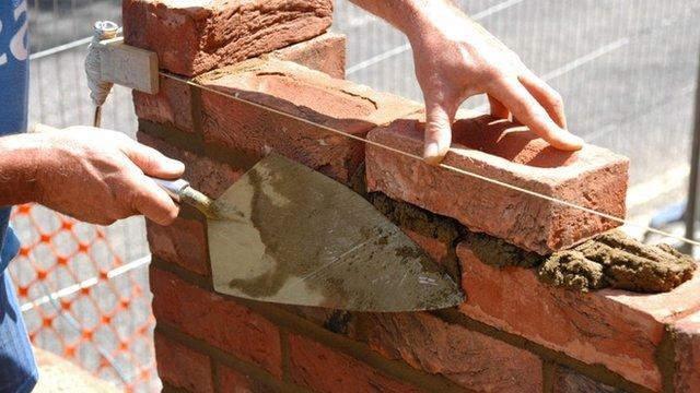 A brick layer builds an extension.