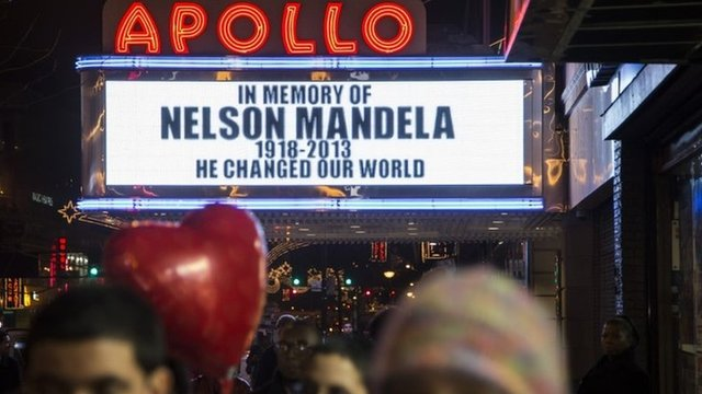 Pedestrians pass beneath the Apollo Theatre marquee commemorating the life of South African leader Nelson Mandela 5 December 2013