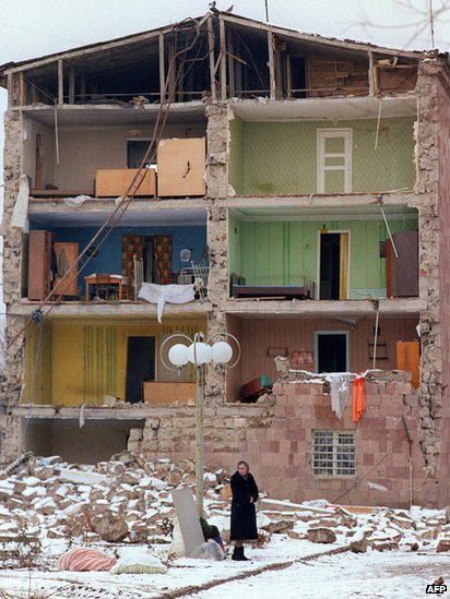 A woman stands near a destroyed building, on December 15, 1988, in the devastated town of Leninakan, after an earthquake hit Armenia, on December 7, 1988.