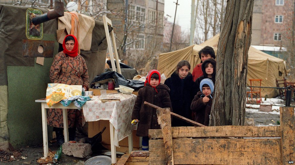 Survivors stand in an improvised camp for homeless in the devastated town of Leninakan, on December 15, 1988, after an earthquake hit Armenia, on December 7, 1988.