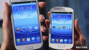 models hold a Samsung Galaxy S and a Galaxy S3 Mini (R) smartphones