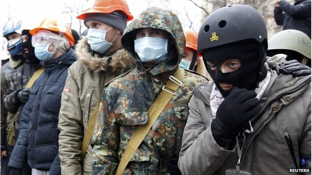 People wear helmets and masks as they attend the rally.