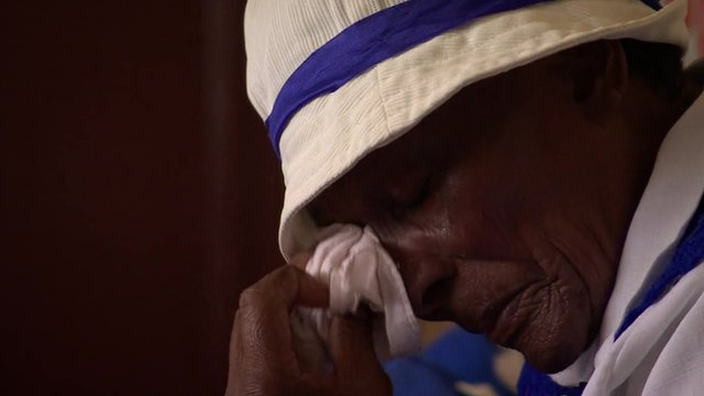 A member of the congregation of a church in Soweto sheds a tear at a memorial service for Nelson Mandela