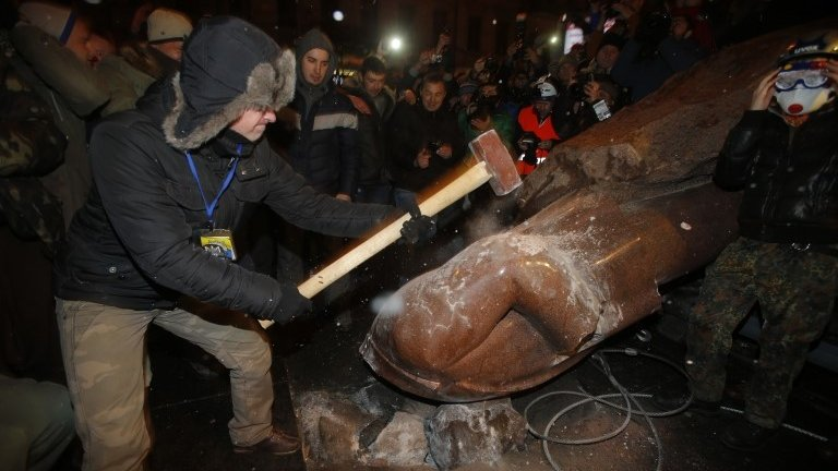 An anti-government protester smashes the statue of Vladimir Lenin with a sledgehammer in Kiev, Ukraine, 8 December 2013