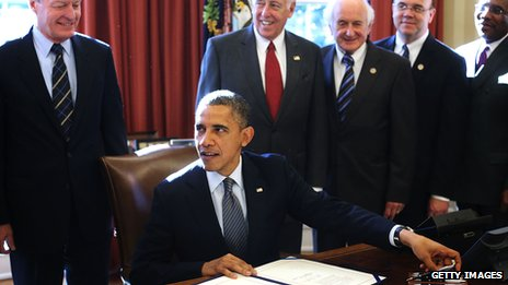 President Obama, surrounded by officials