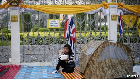 An anti-government protester eats breakfast as she wakes up outside Government House in Bangkok on 10 December 2013