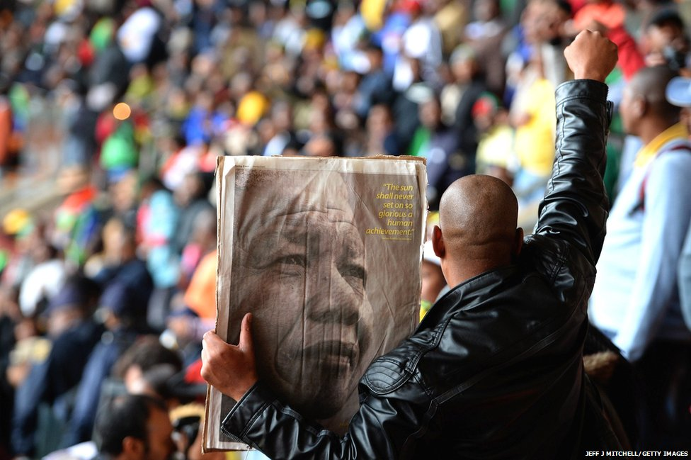 A man holds a poster of Mandela