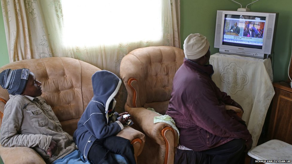 Ndzondzo Mabope sits with family members as they watch a local television station broadcasting live images from former president Nelson Mandela memorial held in Johannesburg