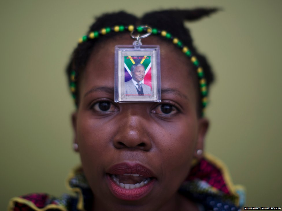 A woman wears a photo of former South African president Nelson Mandela